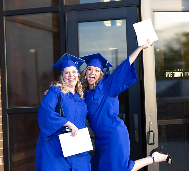 Two students graduating with smiles aspect ratio 682 620